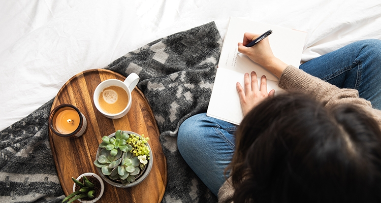 Woman writing next to a tray with coffee, candle and potted succulents 1
