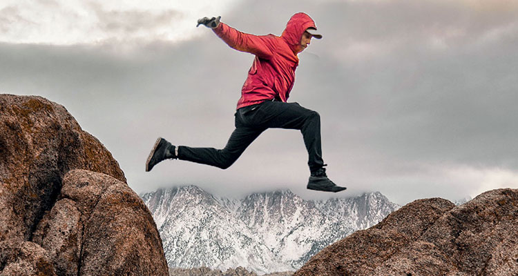 Action shot of a man in a red windbreaker jumping across a ravine