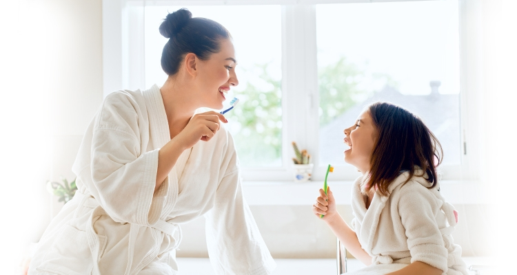 Mother and daughter brushing their teeth together with GLISTER oral care 1