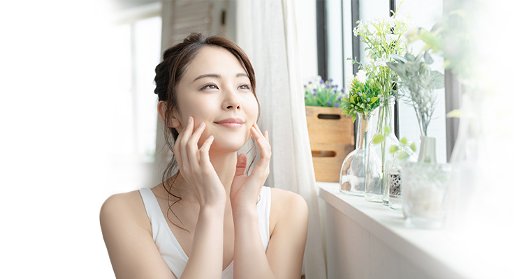 Woman caring for her skin next to a window with flowers