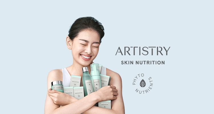 Happy Asian woman holding several ARTISTRY SKIN NUTRITION products to her chest